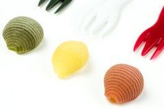 Pastas italianas crudas del conchiglie en un fondo blanco Foto de archivo