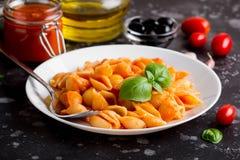 Pastas italianas de la cáscara con la salsa, las aceitunas y la albahaca de tomate, clásicas fotos de archivo