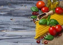 Pastas italianas de la comida, tomate, albahaca, aceite de oliva, pimienta Imagenes de archivo