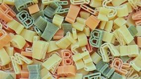 Pastas italianas de los niños del alfabeto de diversos colores cercanos encima de fondo de la rotación de la textura metrajes