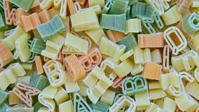 Pastas italianas de los ni?os del alfabeto de diversos colores cercanos encima de fondo de la rotaci?n de la textura metrajes