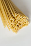 Pastas italianas del bucatini en la superficie blanca Fotografía de archivo libre de regalías