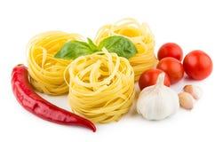 Pastas italianas en jerarquía, tomates, ajo, pimienta y albahaca de la forma Imagen de archivo libre de regalías