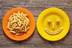Pastas italianas en placa anaranjada y sonrisa con las pastas en un fondo de madera fotos de archivo libres de regalías