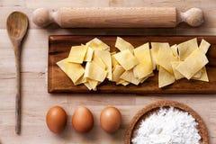 Pastas italianas Rodillo, harina, huevos, cucharón Superficie de madera Foto de archivo