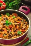 Pastas mediterráneas de la berenjena en pote con los tomates, la pimienta roja y el perejil en fondo gris Imagen de archivo libre de regalías