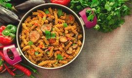 Pastas mediterráneas de la berenjena en pote con los tomates, la pimienta roja y el perejil en fondo gris Foto de archivo