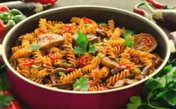 Pastas mediterráneas de la berenjena en pote con los tomates, la pimienta y el perejil en fondo gris Imagen de archivo libre de regalías