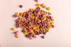 Pastas multicoloras con la adición del tinte vegetal natural Dispersado en un fondo amarillo Visión superior, modelo fotografía de archivo libre de regalías