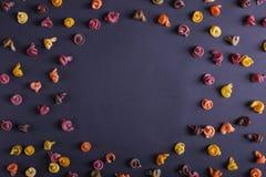 Pastas multicoloras con la adición del tinte vegetal natural Dispersado en un fondo negro, espacio de la copia Visión superior, m imagenes de archivo