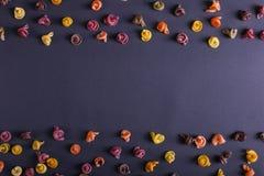 Pastas multicoloras con la adición del tinte vegetal natural Dispersado en un fondo negro, espacio de la copia Visión superior, m fotos de archivo