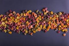 Pastas multicoloras con la adición del tinte vegetal natural Dispersado en un fondo negro Visión superior, modelo foto de archivo