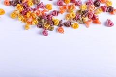 Pastas multicoloras con la adición del tinte vegetal natural Dispersado en una tabla blanca Visión superior, espacio de la copia fotos de archivo libres de regalías