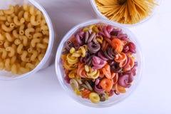 Pastas multicoloras con la adición del tinte vegetal natural En un tarro en una tabla blanca Visión superior, espacio de la copia imagenes de archivo