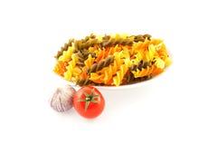 Pastas multicoloras, un tomate y ajo Imagen de archivo