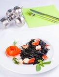 Pastas negras del tagliatelle con los cubos del cangrejo Fotos de archivo libres de regalías