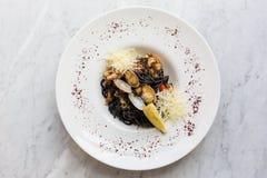 Pastas negras servidas con los mariscos Tallarines negros con los mejillones, calamar, pulpos con la adición del queso parmesano Imagen de archivo libre de regalías
