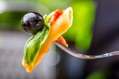 Pastas Penne con la aceituna negra boloñesa de la salsa, del queso parmesano del tomate y la albahaca en una bifurcación Alimento Fotos de archivo