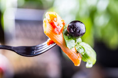 Pastas Penne con la aceituna negra boloñesa de la salsa, del queso parmesano del tomate y la albahaca en una bifurcación Alimento Imagen de archivo