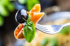 Pastas Penne con la aceituna negra boloñesa de la salsa, del queso parmesano del tomate y la albahaca en una bifurcación Alimento Foto de archivo libre de regalías