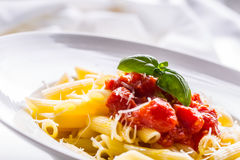 Pastas Penne con la salsa, el queso parmesano y la albahaca boloñeses del tomate en una bifurcación Alimento mediterráneo Cocina  Fotografía de archivo