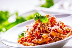 Pastas Penne con la salsa, el queso parmesano y la albahaca boloñeses del tomate en una bifurcación Alimento mediterráneo Cocina  Imágenes de archivo libres de regalías