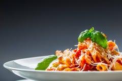 Pastas Penne con la salsa, el queso parmesano y la albahaca boloñeses del tomate en una bifurcación Alimento mediterráneo Cocina  Imagenes de archivo