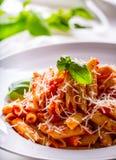 Pastas Penne con la salsa, el queso parmesano y la albahaca boloñeses del tomate en una bifurcación Alimento mediterráneo Cocina  Fotografía de archivo libre de regalías