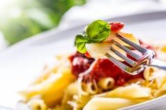 Pastas Penne con la salsa, el queso parmesano y la albahaca boloñeses del tomate en una bifurcación Alimento mediterráneo Cocina  Fotos de archivo