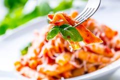 Pastas Penne con la salsa, el queso parmesano y la albahaca boloñeses del tomate en una bifurcación Alimento mediterráneo Cocina  Foto de archivo