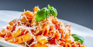 Pastas Penne con la salsa, el queso parmesano y la albahaca boloñeses del tomate en una bifurcación Alimento mediterráneo Cocina  Fotos de archivo libres de regalías