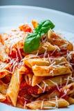 Pastas Penne con la salsa, el queso parmesano y la albahaca boloñeses del tomate en una bifurcación Alimento mediterráneo Cocina  Imagen de archivo