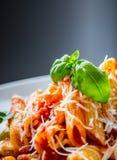 Pastas Penne con la salsa, el queso parmesano y la albahaca boloñeses del tomate en una bifurcación Alimento mediterráneo Cocina  Foto de archivo libre de regalías