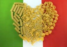 Pastas presentadas en la forma de un corazón en los colores de fondo de la bandera italiana Fotografía de archivo libre de regalías