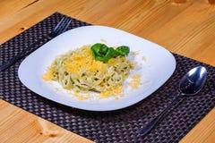 Pastas sabrosas con queso y verdes en la placa blanca Foto de archivo libre de regalías