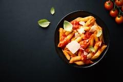 Pastas sabrosas del tomate en cuenco en oscuridad Imagen de archivo