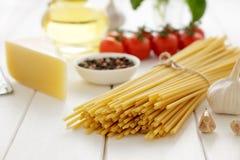 Pastas secas con queso, los tomates, el ajo y el aceite en el fondo de madera blanco Imagen de archivo libre de regalías