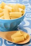 Pastas sin procesar en un tazón de fuente azul Imágenes de archivo libres de regalías