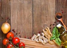 Pastas, tomates, cebolla, aceite de oliva y albahaca en fondo de madera Foto de archivo libre de regalías
