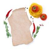 Pastas, tomates, especias y un trozo de papel para escribir la receta Foto de archivo