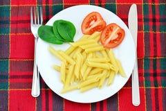 Pastas, tomates y espinaca en la placa fotografía de archivo