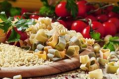 Pastas tricolores en la forma de corazones en una tabla de madera, toma imagen de archivo libre de regalías