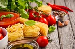 Pastas, verduras, hierbas y especias para la comida italiana en la tabla de madera rústica Foto de archivo