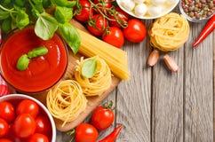 Pastas, verduras, hierbas y especias para la comida italiana en la tabla de madera rústica Foto de archivo libre de regalías
