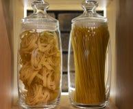 Pastas y espaguetis en un estante en un tarro de cristal en un interior moderno fotografía de archivo libre de regalías