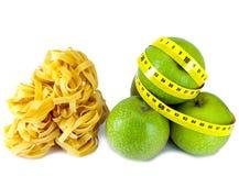 Pastas y manzana italianas de la jerarquía del fettuccine con una cinta métrica. Aún-vida en un fondo blanco Fotos de archivo