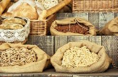 Pastas y pasteles en bolsos en el tablero retro de madera Imágenes de archivo libres de regalías