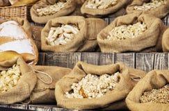 Pastas y pasteles en bolsos grandes en el tablero retro de madera, comida m Foto de archivo