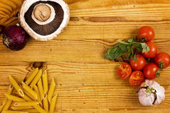 Pastas y verduras en la tabla de cortar Fotos de archivo