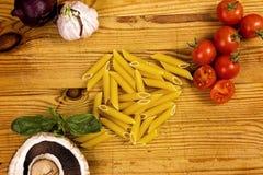Pastas y verduras en la tabla de cortar imagen de archivo libre de regalías